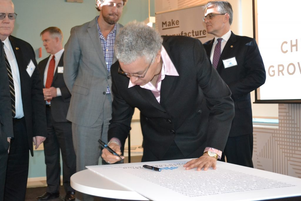 President Preckwinkle signs founding document for display on behalf of Cook County.